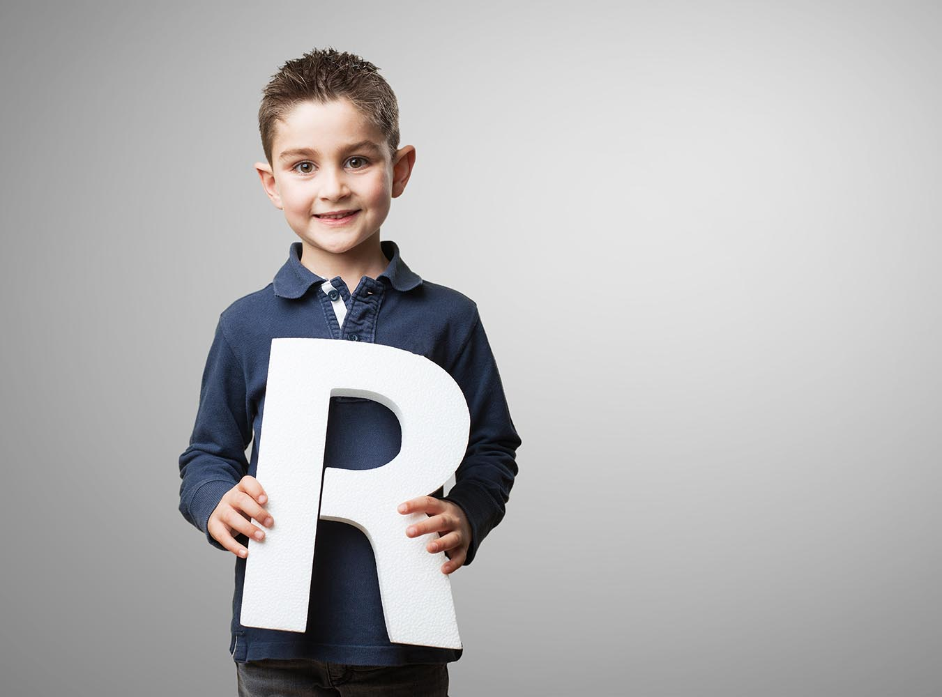 Child Holding Letter R in Hand